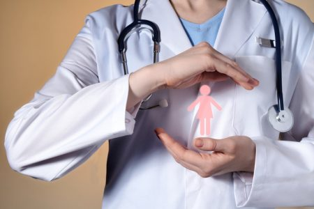 A woman doctor holds a woman's pictograph in her hands. Female doctor with a stethoscope gesticulating on a beige background.